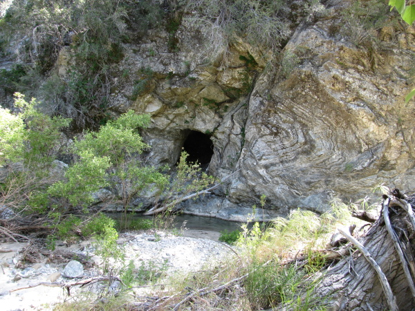 A cave in the cliffside above the water.