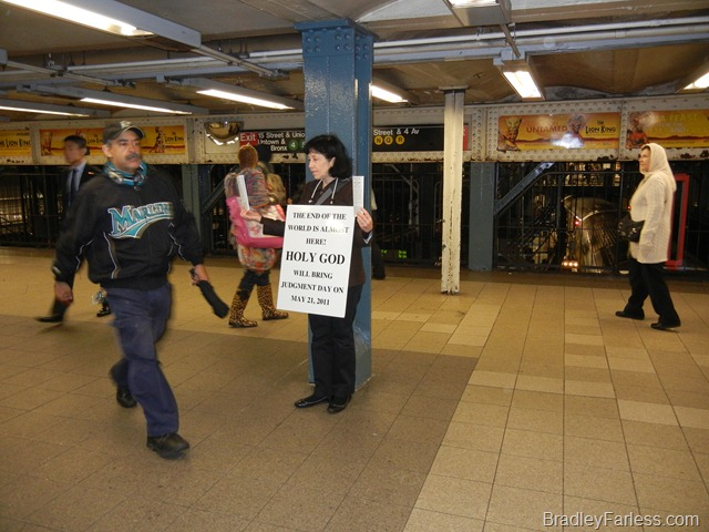 Lady in Union Square train station with a sign stating the world will end on May 21, 2011.