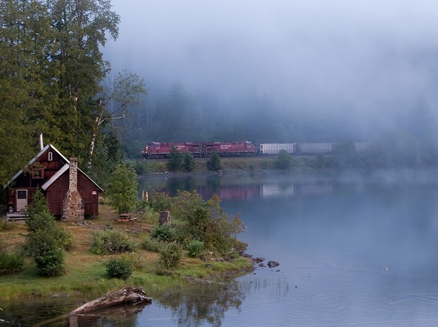 Train pass through a foggy lakefront morning, surrounded by green at Three Valley in Revelstoke, British Columbia, Canada