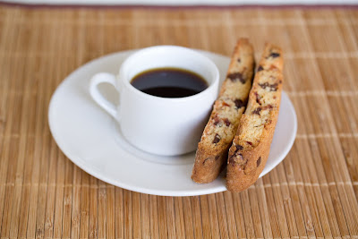 Photo of a cup of coffee on a saucer with two pieces of biscotti