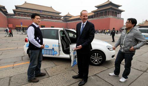 4月6日,大众汽车集团(中国)总裁兼CEO倪凯铭(中)在故宫邀请游客体验高尔夫电动车。新华社.jpg