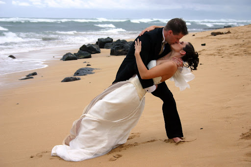 A bride and groom share a kiss on the beachwearing bridal gown