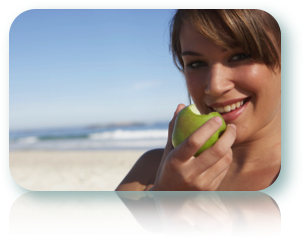 Woman at the beach biting into a green apple.