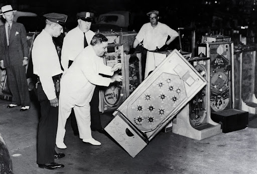 New York Mayor Fiorello La Guardia Knocks Over a Confiscated Bally Bumper Pinball Machine