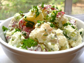 Side view of a bowl full of picnic potato salad, garnished with parsley, window in the background.