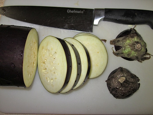 eggplant sliced into 1/2 inch rounds with knife