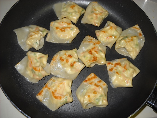 boiled wontons in frying pan to brown them