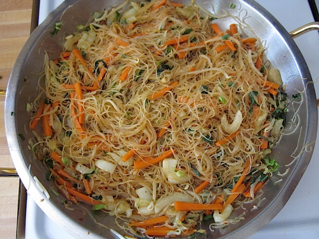soy sauce mixture added to noodles and veggies in pan