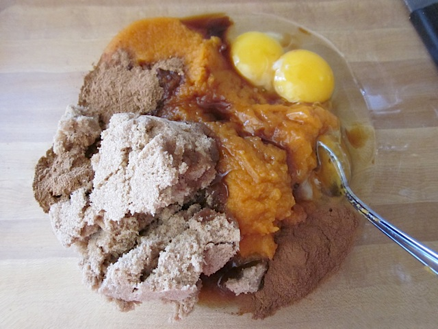 pumpkin custard ingredients in clear mixing bowl (pumpkin puree, brown sugar, eggs, cinnamon, pumpkin pie spice and vanilla)