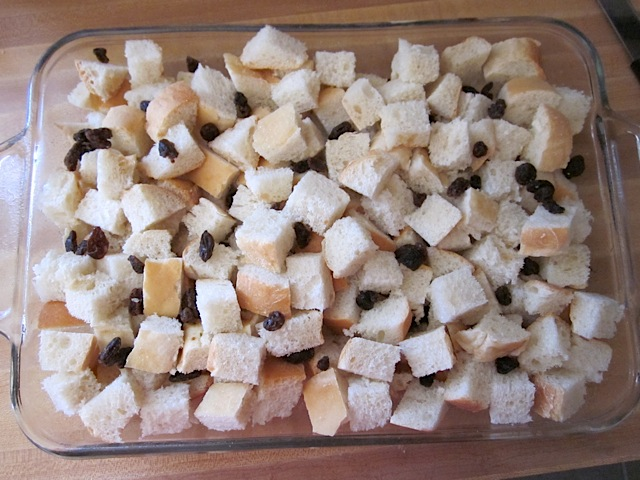 Cubes of bread and raisins in baking pan
