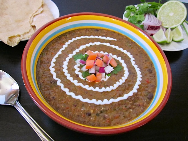 Black Bean and Roasted Salsa Soup in colorful bowl with garnishes and spoon on side