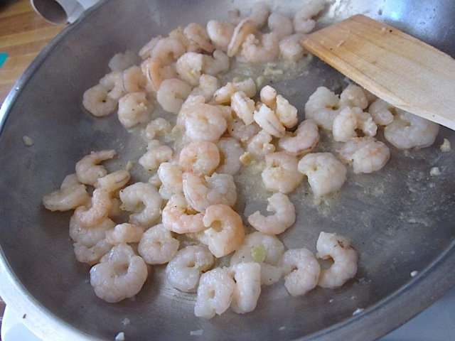 cooked shrimp in pan with wooden spoon