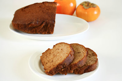 photo of sliced persimmon bread with a loaf in the background
