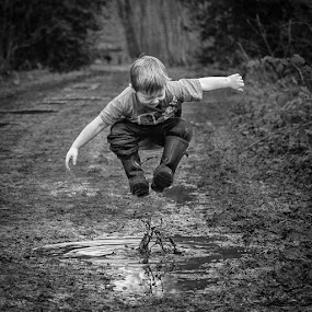 Everyone Likes Jumping Up And Down In Muddy Puddles by Dan Horton-Szar ARPS - Black & White Portraits & People ( countryside, monochrome, canterbury, wood, black and white, kent, children, forest, rural, jump, blean wood, mud, family, path, woodland, puddle, boy,  )
