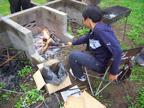 尾瀬 奥会津 檜枝岐村七入オートキャンプ場 朝の焚火をする少年
