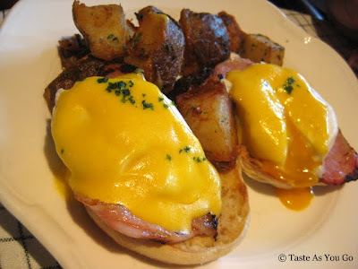 Classic Eggs Benedict with Canadian Bacon and Hollandaise on a Muffin and Herb Roasted Potatoes at The Standard Grill in New York, NY - Photo by Taste As You Go