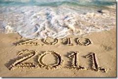 foto de uma praia com as inscrições 2010 e 2011 escritas na areia. As ondas do mar cobrem parte da inscrição 2010.