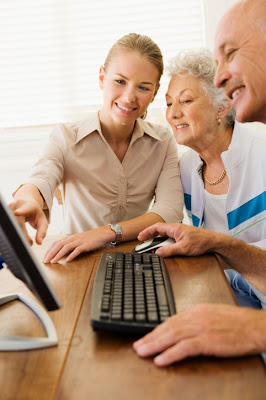 A young lady assisting an elderly couple on the computer.