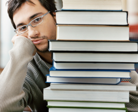 a disgruntled looking young man sitting behind a stack of text books