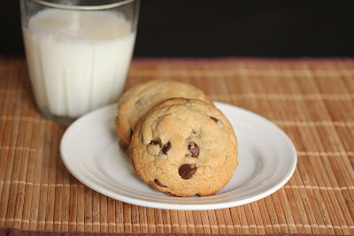 photo of chocolate chip cookies on a plate with a glass of milk