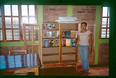 Karlita, the first youth centre coordinator, showing some of the sparse resources held in the centre, 2006