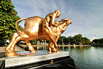 The man with buffalo sculpture on the left side of the lagoon.