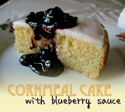 A close up photo of a slice of lemon cornmeal cake topped with blueberry sauce.