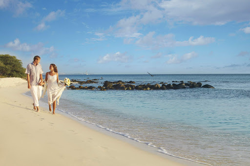A bride and groom take a quiet stroll on the beach in Aruba.