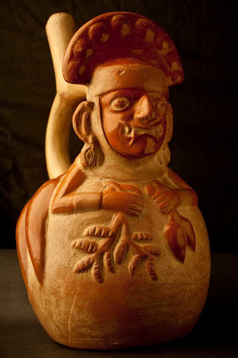 Sculptural ceramic ceremonial vessel that represents Ai Apaec, mythological hero of the Moche transformed in a chili plant and holding a chili plant and a peanut plant ML003286