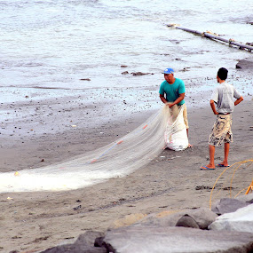 Fisherman gathering his net by Leong Jeam Wong - People Professional People ( bali, sea, trawling, beach, net, fisherman )