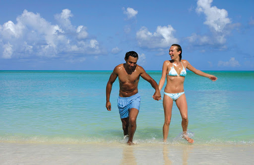 A couple frolics in the warm afternoon surf at the Jolly Beach Resort in Antigua and Barbuda.