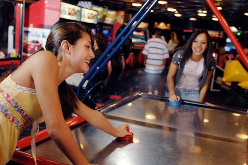 Girls play a game of air hockey at Quarter Masters, the young people's arcade on deck 9 at midship of Disney Magic and the Disney Wonder next to Quiet Cove Pool. The arcade also features tons of videogames.