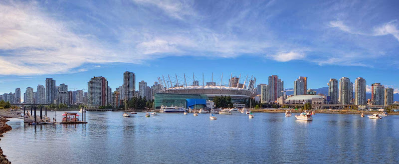 False Creek, BC Place and downtown Vancouver high-rise buildings under a blue sky