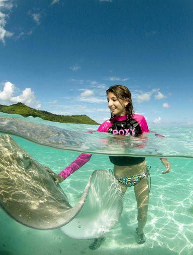 Girl-Plays-With-StingRays-BoraBora - A girl strokes a stingray — they're safe — in the warm Bora Bora waters.