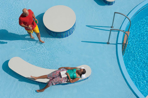 Disney-Dream-guest-lounging-by-pool - Relax and get to that book you've been meaning to read while lounging by the Quiet Cove Pool on Disney Dream.