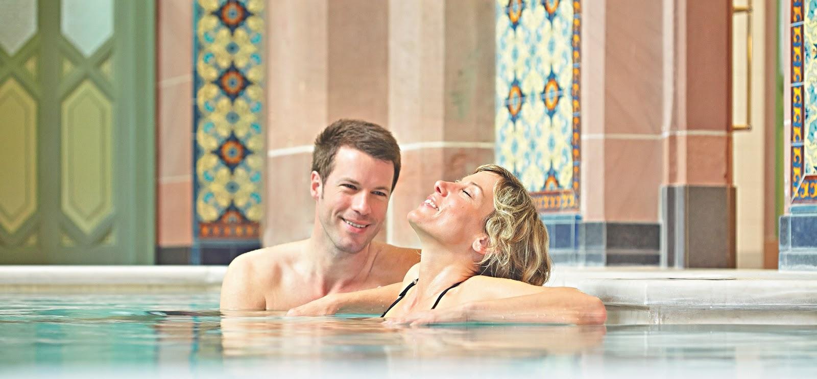 Ein junges Paar genießt seine Zeit im Wasserbecken des Palais Thermal