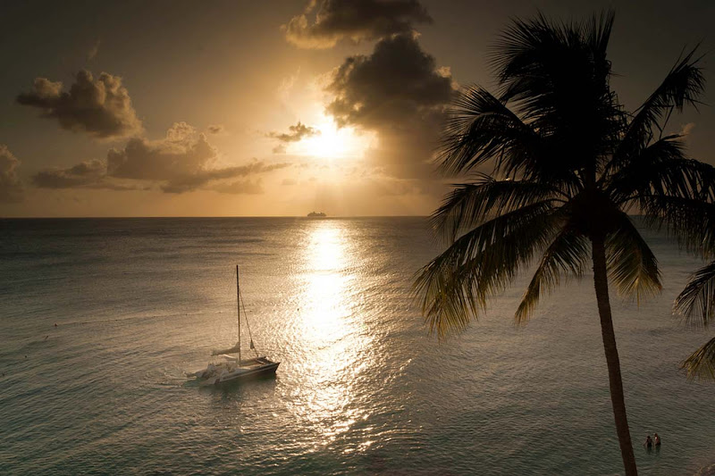 The sun sets on a catamaran on a quiet bay on Barbados.