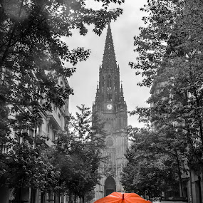 Red Under Rain by Justin Murazzo - City,  Street & Park  Street Scenes ( old, gothic, bright, street, kalea, good, leaves, people, spain, city, religion, center, contrast, sky, cars, light, black, church, umbrella, white, tourism, overcast, country, loiola, trees, cathedral, day, roman, religious, sidewalk, humanity, echave, del buen pastor, beauty, drip, daytime, shepherd, style, cloudy, crowd, rain, clouds, water, ominous, building, selective color, society, afternoon, clock, beautiful, scenic, gray, point, catholic, red, pwc, steeple, stand, san sebastian, drops, square, basque, daylight,  )