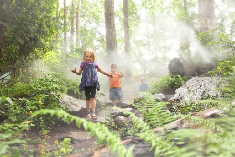 Children play in the forest at Capilano Suspension Bridge Park in Vancouver, British Columbia.