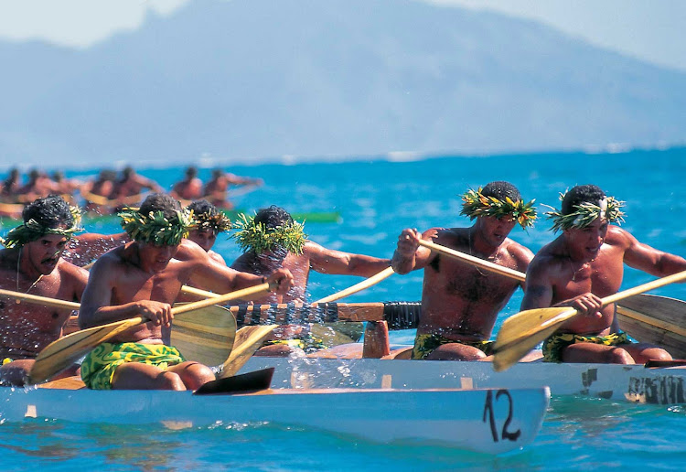 "Tahitian outrigger races feature paddlers dressed in colorful pareos and traditional ""heis"" and leis for races and demonstrations."