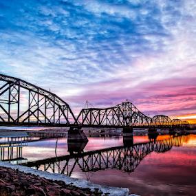 Sunset Crossing by Bob Grandpre - Buildings & Architecture Bridges & Suspended Structures ( water, clouds, train bridge, color, sunset, shoreline, refeletions, missouri river,  )