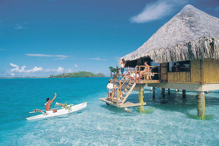 A canoeist approaching a visitor's bungalow at the InterContinental Bora Bora Le Moana Resort.