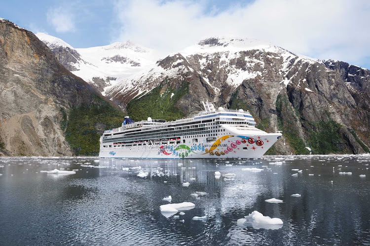 Norwegian Pearl cruising in Alaska waters against a backdrop of rugged coastline and snow-capped peaks.