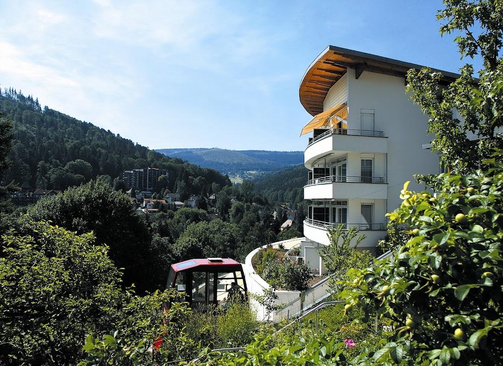 Du siehst die Außenansicht des Schwarzwald Panorama Hotels und die Umgebung des Hotels, dunkle Wälder und Täler des Schwarzwaldes.