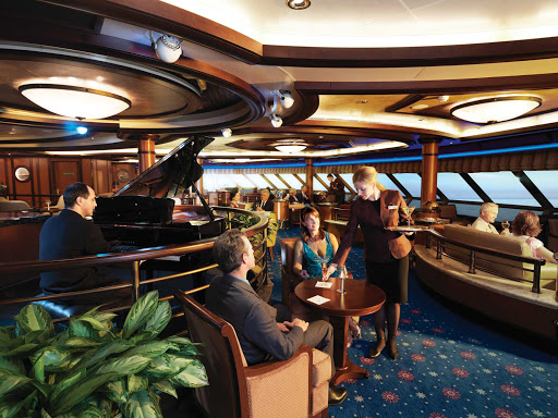 Enjoy your favorite martini or cocktail with panoramic views over the bow of the ship at the Commodore Club aboard Queen Victoria.