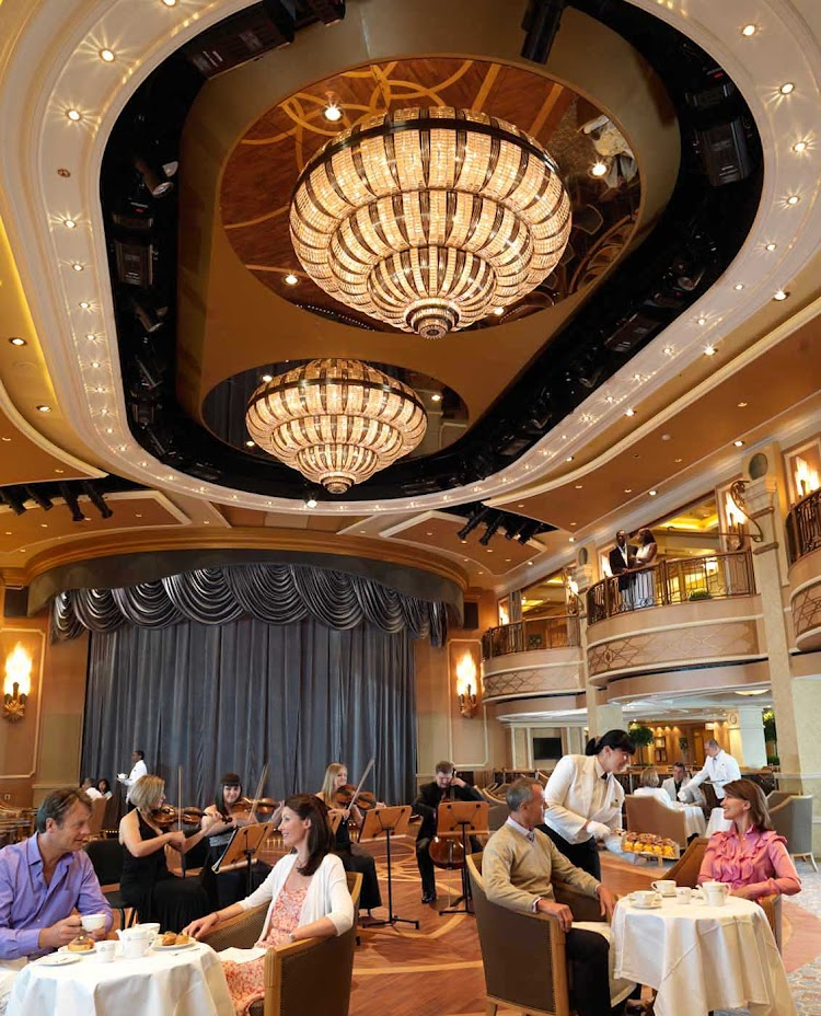 A view of the elegant Queens Room ballroom aboard Queen Elizabeth, where white-gloved waiters serve cucumber sandwiches, scones and tea accompanied by orchestral music.