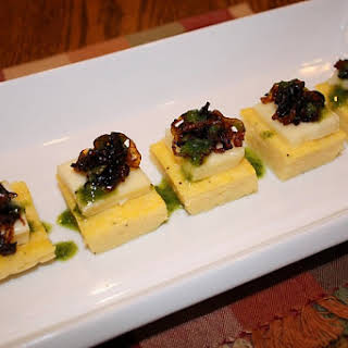 Polenta Cakes with Caramelized Onions, Brie and Basil Oil.