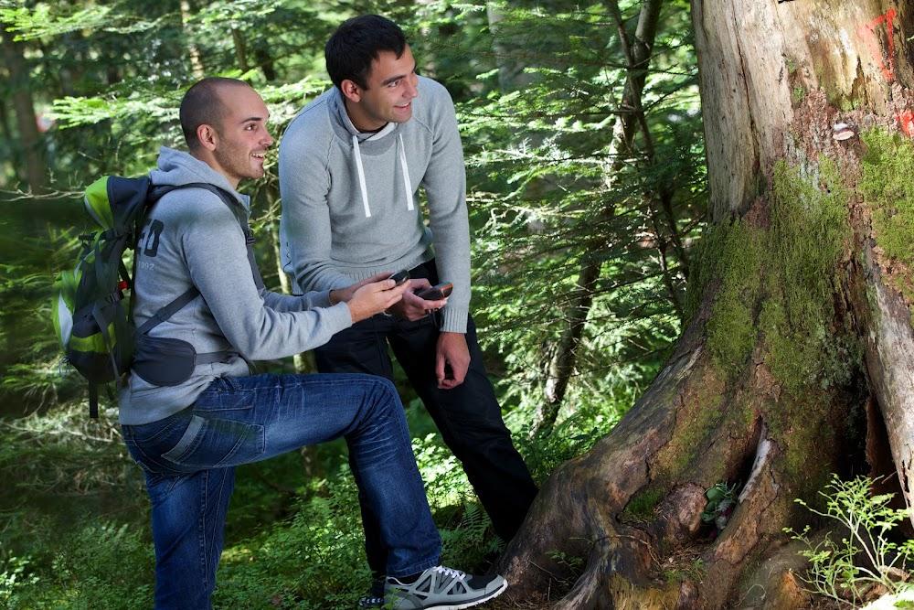 Du siehst zwei junge Männer im Wald, bei einem Baumstamm und mit einem GPS Gerät in der Hand.